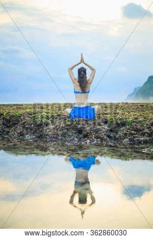 Young Woman, Meditating, Practicing Yoga And Pranayama At The Beach. Sunset Yoga Practice. Hands Rai