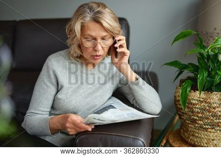 Adult Woman Reading Newspaper With Phone In Hands.news, Press, Media, Holidays And People Concept .