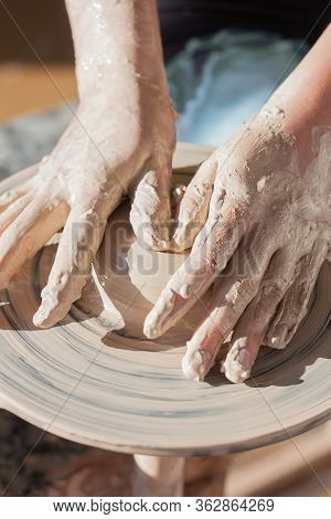 The Girl Is Engaged In Pottery In The Studio On The Pottery Wheel. The Studio Is Flooded With Bright