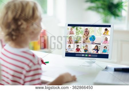 Online Remote Learning. School Kids With Computer Having Video Conference Chat With Teacher And Clas