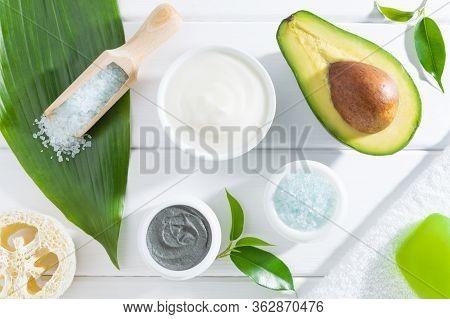 Natural Spa Skin Care Cosmetics: Cream, Cosmetic Clay, Sea Salt, Loofah Sponge, Towel And Avocado On