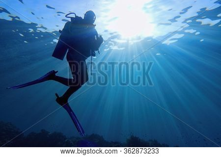 Life-giving Sunlight Underwater. Sun Beams Shinning Underwater And Scuba Diver Silhouette In The Blu