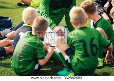 Young Boys In Football Team Listening To Coach. Coach Giving Instruction To His Kids Soccer Team. Fo