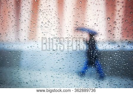 Person with an umbrella walking past a window with raindrops, shallow focus on raindrops