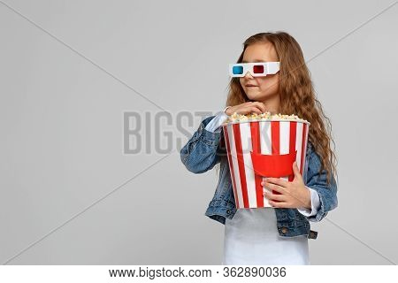 Cute Child Girl Wearing Red-blue 3d Glasses Having Fun And Holding Popcorn Bucket Isolated On Gray B