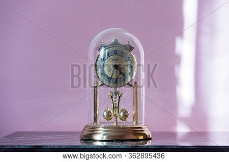 Mantel Clock With Glass Dome & Rotating Pendulum. Period Clock With Oscillating Mechanism On An Old
