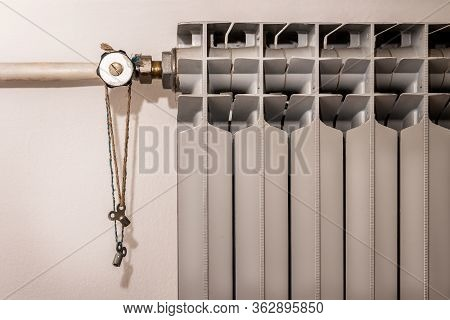 Close Up Heating Radiator With Radiator Keys Brass Air Vent Clock Type Hanging On A Rope. Central He