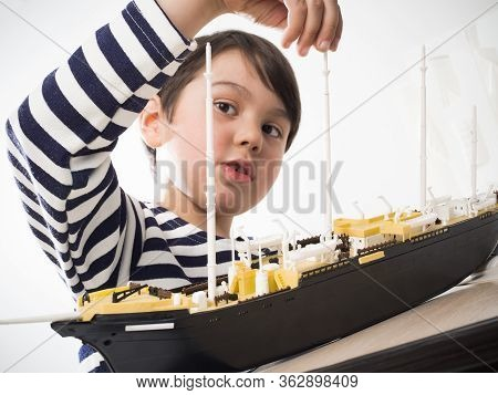 A Small Child Builds A Model Ship