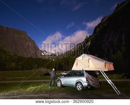 Grossglockner, Austria - July 14, 2019: Back View Of Traveler Standing Near Car With Camping Tent On