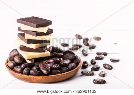 Stack Of Raw Dark Bitter Chocolate And Cocoa Butter With Cocoa Beans On Old Rustic White Table.