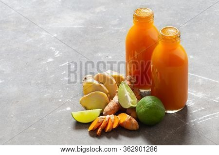 Healthy Drink From Turmeric And Ginger Roots And Lime In Small Bottles On Grey Concrete Background W