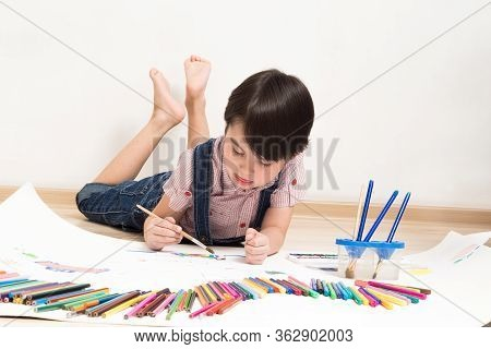 The Child Draws Drawings With Pencils And Paints