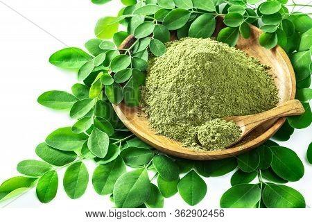 Moringa Powder (moringa Oleifera) In Wooden Bowl With Original Fresh Moringa Leaves Isolated On Whit