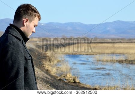 Young Man In Coat Looking Down With Upset Face Near Swamp And Rail. Depressive Concept Loss Of Money