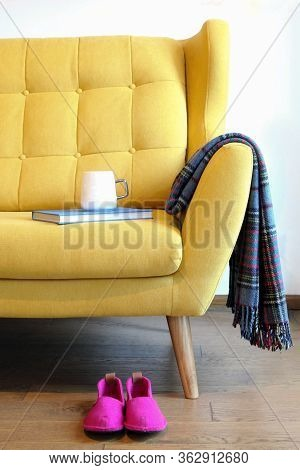 Cup Of Tea And Blue Book On A Yellow Coach. Still Life Details In Home Interior Of Living Room. Cozy