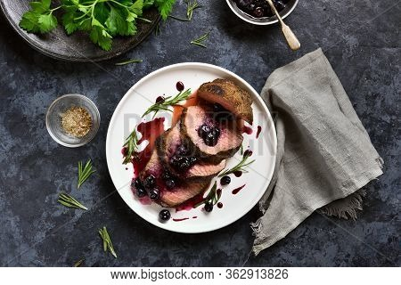 Grilled Beef With Blueberry Sauce On White Plate Over Blue Stone Background. Tasty Medium Rare Roast