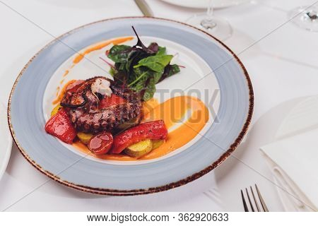 Grilled Octopus With Vegetables And Cuttlefish Sauce. Restaurant, Lifestyle, Travel Food - Grilled O