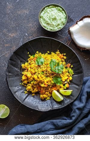 Indian Cuisine. Poha Or Flattened Rice Typically Western Indian Breakfast On Black Plate With Coconu