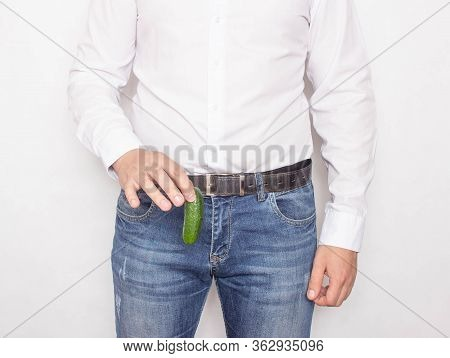 A Man Holds A Small Cucumber In His Hand. Penis Size Concept, Penis Enlargement And Thickening, Body