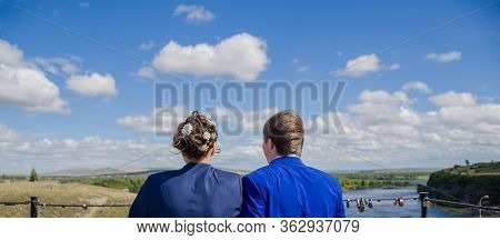 A Guy And A Girl Are Looking To The Future. The Newlyweds Stand Side By Side Against The Blue Sky, A