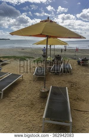 Tamarin Beach, Mauritius, December 2019 - Parasols And Beach Loungers In Front Of A Hotel Resort At
