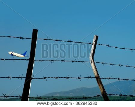 Transportation image of flying commercial passenger airplane and barbed wire fence over blue sky