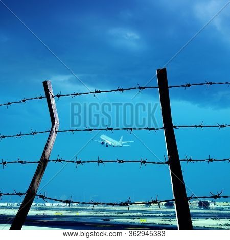 Transportation image of flying commercial passenger airplane and barbed wire fence over airport and blue sky in Qatar airport
