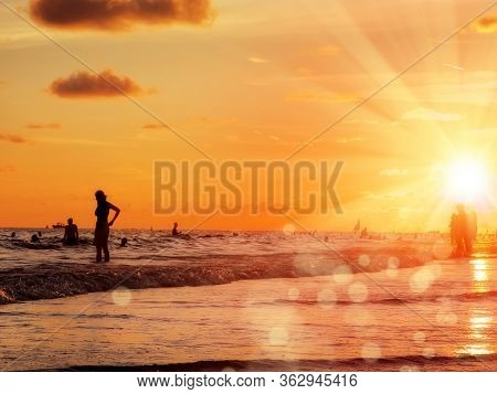 group of silhouetted people on public beach over orange colored sunset sky in Siesta key, Sarasota, Florida