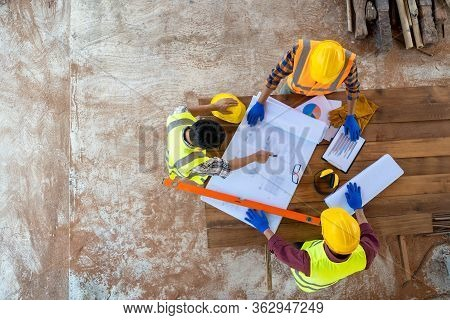 High Angle View Of Engineer And Architect Discussing Building Plan At Construction Site,group Of Bui