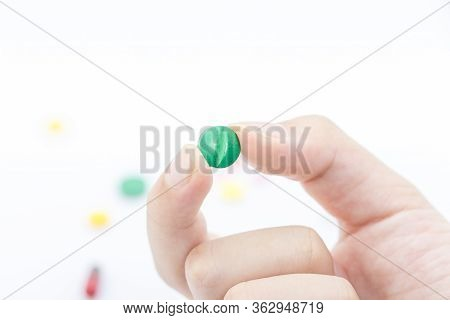 Hand Of Man Holding Green Pill. Close Up