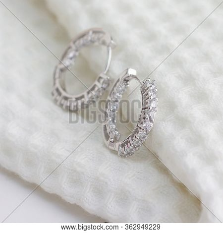A Pair Of Beautiful 925 Sterling Silver Earrings Decorated With Diamonds On White Cloth