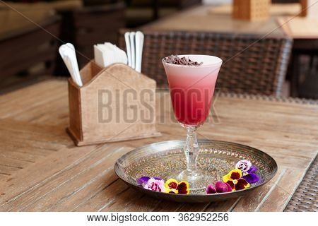 Red cocktail with froth, violet flowers and chocolate shavings on restaurant table