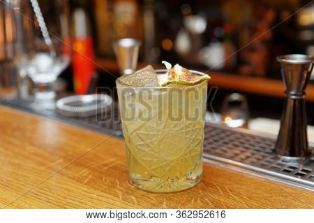 Simple cocktail with apple chips served on the rocks