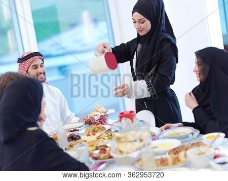 Eid Mubarak Muslim family having Iftar dinner drinking water to break feast. Eating traditional food during Ramadan feasting month at home. The Islamic Halal Eating and Drinking at modern western Isla