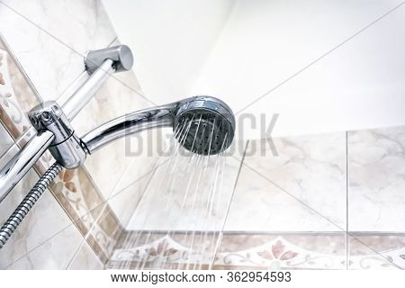 Interior Of A Shower With Water Flowing From The Shower Head. Droplets And Moisture. Walls With Deco
