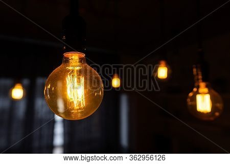 Close-up Of Incandescent Light Bulbs Hanging In The Dark Room. Inefficient Filament Light Bulbs Wast