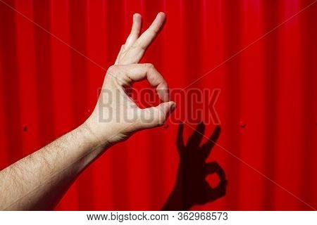 Gesture Okay Fingers On A Red Background. Ok Hand Gesture. Sign Ok.