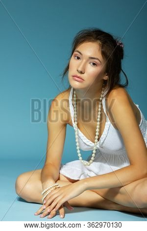 Beautiful girl in white dress and pearl beads sitting at studio on blue background. Portrait of charming young woman