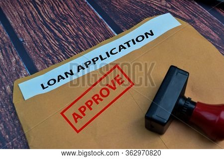 Red Handle Rubber Stamper And Approve Text And Loan Application Doceument Isolated On Wooden Table B