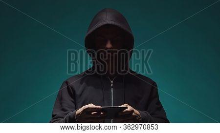 Portrait Of Computer Hacker In Hoodie. Obscured Dark Face. Data Thief, Internet Fraud, Darknet And C