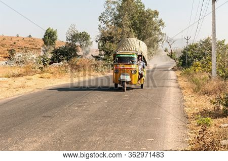 Puttaparthi, Andhra Pradesh, India - January 12, 2013: Indian People Travel In Rickshaw Taxi Along T