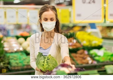 shopping, food, sale, consumerism and people concept - happy woman in face protective medical mask for protection from virus disease buying savoy at grocery store or supermarket