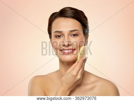 beauty, people and skincare concept - young woman cleaning face with exfoliating sponge over beige background