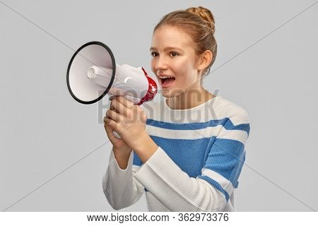 communication, feminism and rights concept - teenage girl speaking to megaphone over grey background
