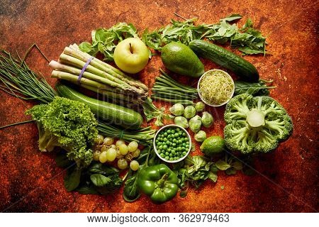Fresh, natural, green vegetables, fruits and herbs assortment placed on a rusty metal background. Top view.