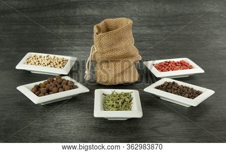 Burlap Sack And Natural Spices On Dark Background. Jute Sack Mock Up And Herbs. Copy Space For Text.