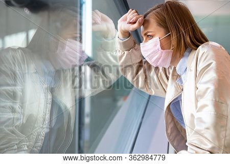 Depressed Woman Wearing Medical Face Mask, Looking Out The Window At An Empty City, Loss Job Due To