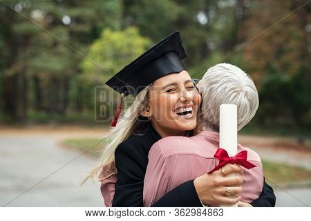 Enthusiastic graduated daughter holding degree hugging mother in campus. Young female student graduate hugging her mom at graduation ceremony. Excited college student with the graduation gown and hat.