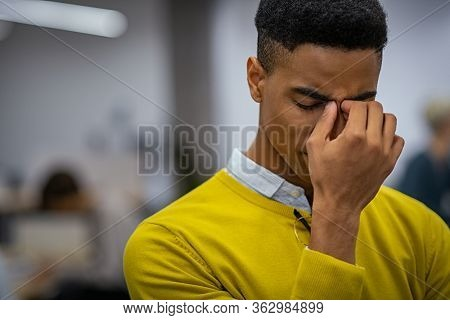 Portrait of an upset young businessman. Black depressed business man with a terrible headache. Stressed african man feeling strain in eyes after working for long hours on computer: overwork, burnout.