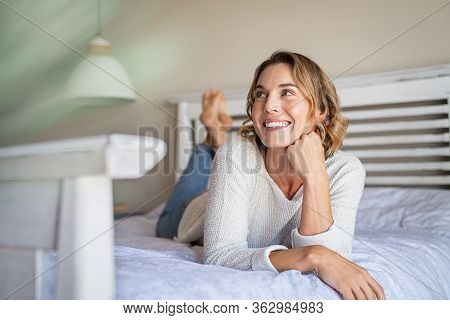 Happy pensive young woman lying and thinking on bed. Thoughtful beautiful girl lying on bed while looking up. Smiling blonde woman contemplating the future at home.